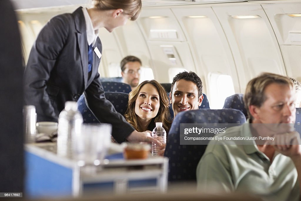 flight attendant serving customers on an airplane : Stock Photo