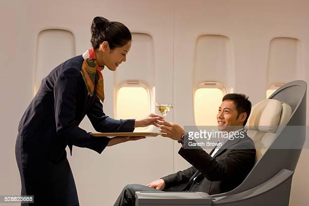Flight attendant serving man martini