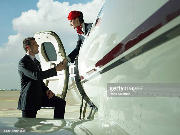 Flight attendant shaking hands with man boarding private plane on airfield, side view