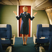 Flight attendant showing where emergency exits are on plane