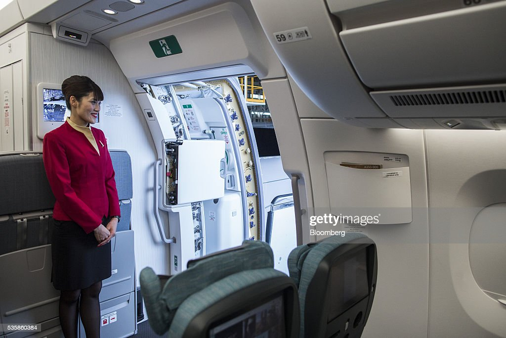A flight attendant stands near a cabin door onboard an Airbus Group SE A350-900 aircraft operated by Cathay Pacific Ltd. during a media event in Hong Kong, China, on Monday, May 30, 2016. Airbus stuck to plans to increase plane deliveries this year as it pushes to overcome a series of problems affecting production of its newest aircraft. Photographer: Justin Chin/Bloomberg via Getty Images