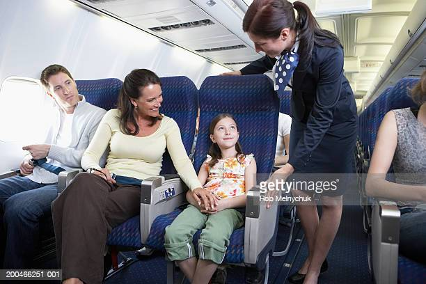 Flight attendant talking to man and woman with daughter (6-8) on plane