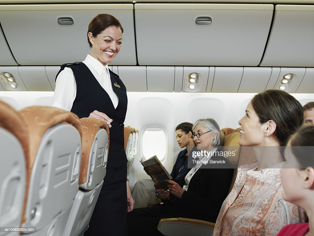 Flight attendant talking with passengers including child (10-11) on airplane