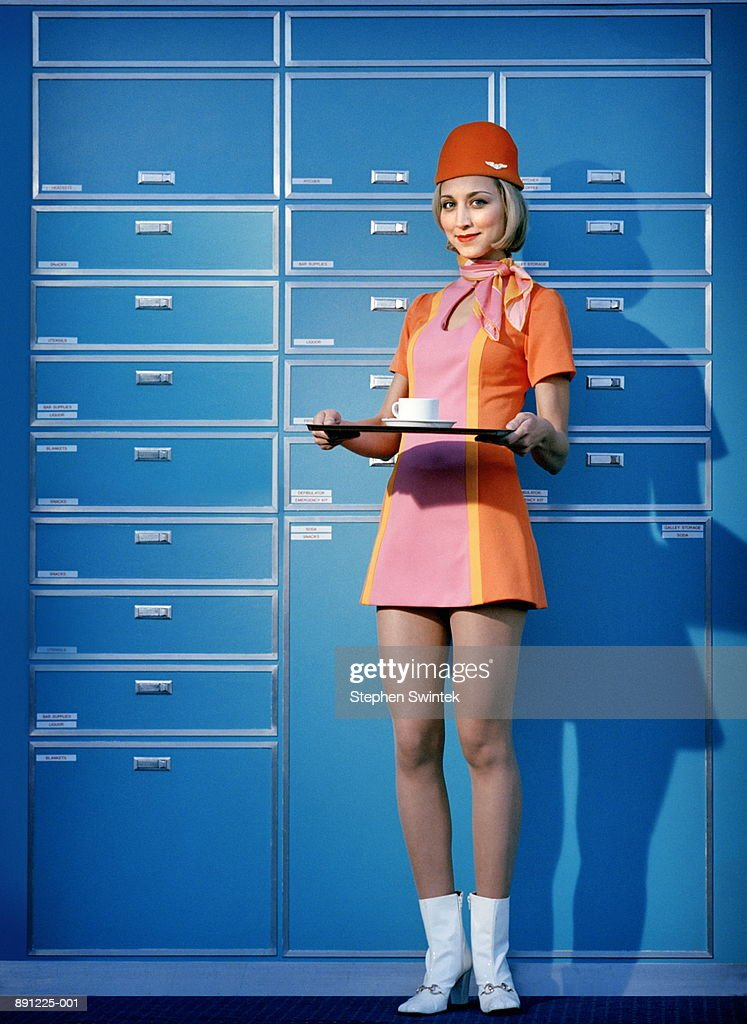 Flight attendant wearing 60's attire, holding tray with cup on it : Stock Photo
