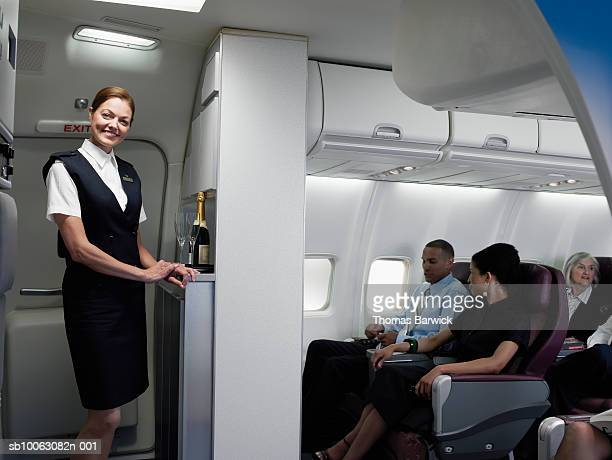 Flight attendant with champagne in service area, passengers in background