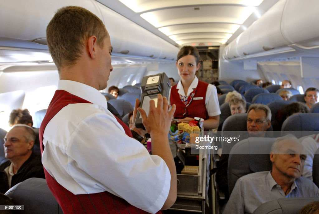 Flight attendants Enrico Berger left and Nina Schuster serve passengers on an Air Berlin flight from Berlin Germany to Alicante Spain Friday April 28...