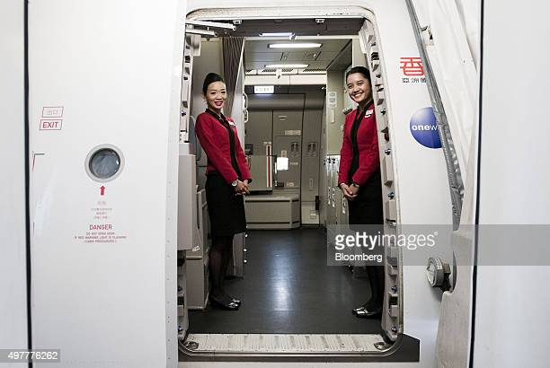 Flight attendants stand at the cabin door to welcome attendees onboard a flight of Hong Kong Dragon Airlines Ltd a unit of Cathay Pacific Airways Ltd...