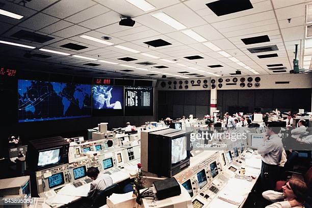 Flight controllers in the control room monitor two space walkers on television during the STS61 Mission
