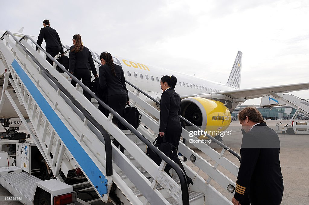 Flight crew board an Airbus A320 aircraft operated by Vueling Airlines SA at EL Prat airport in Barcelona, Spain, on Wednesday, Dec. 19, 2012. International Consolidated Airlines Group SA won't require European Union approval to buy 100 percent of low-cost carrier Vueling Airlines SA, the EU's antitrust chief said. Photographer: Stefano Buonamici/Bloomberg via Getty Images