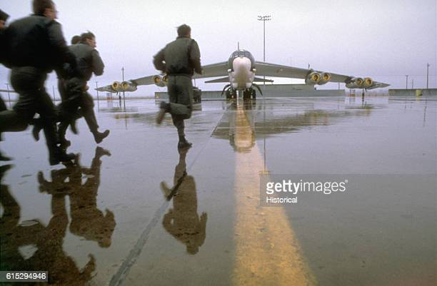 A flight crew runs to a B52 Stratofortress aircraft to begin their alert mission | Location Grank Forks Air Force Base North Dakota USA