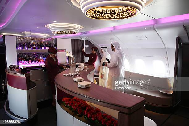 Flight crew show visitors through the bar area for business class passengers aboard an Airbus A380800 aircraft operated by Qatar Airways Ltd on the...