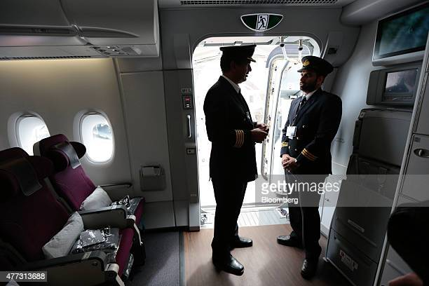 Flight crew stand in the passenger access door to an Airbus SAS A380 aircraft operated by Qatar Airways Ltd on day two of the 51st International...