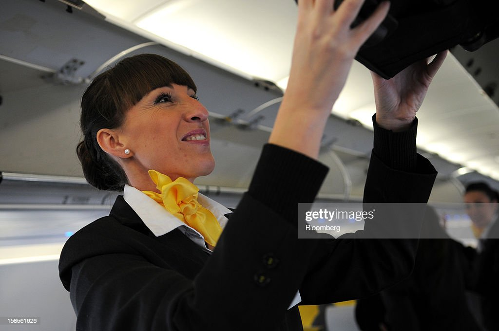 Flight crew stow their luggage in overhead lockers aboard a Vueling Airlines SA Airbus A320 aircraft at El Prat airport in Barcelona, Spain, on Wednesday, Dec. 19, 2012. International Consolidated Airlines Group SA won't require European Union approval to buy 100 percent of low-cost carrier Vueling Airlines SA, the EU's antitrust chief said. Photographer: Stefano Buonamici/Bloomberg via Getty Images