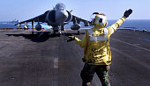 Flight Deck Handler directs an AV8B 'Harrier' prior to takeoff from the USS Peleliu for a mission over Afghanistan NOvember 2 2001 in support of...