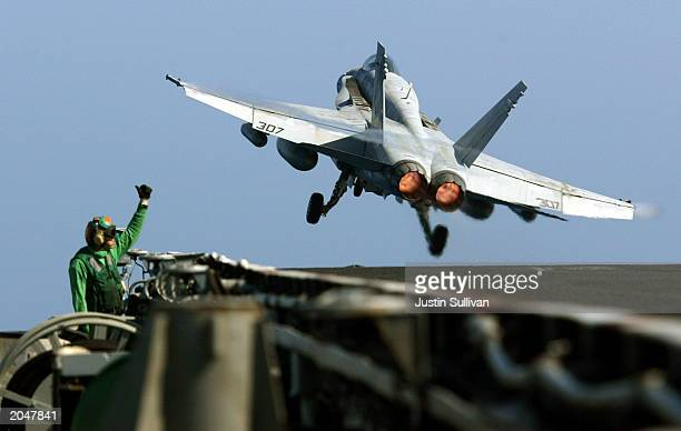 A flight deck worker gives the tumbsup as an F/A18 Hornet takes off from the USS Constellation during final flyoffs June 1 2003 in the Pacific Ocean...