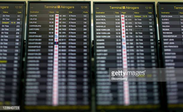 Flight departure and arrival times appear on a board in this photo taken with a tiltshift lens in the Toronto Pearson International Airport in...