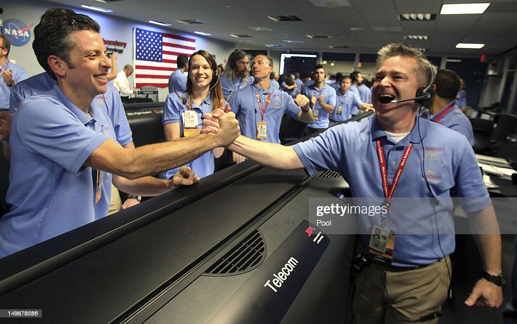 Flight director Keith Comeaux, right, celebrates with Martin Greco after a successful landing inside the Spaceflight Operations Facility for NASA's Mars Science Laboratory Curiosity rover at Jet Propulsion Laboratory on August 5, 2012 in Pasadena, California. The MSL Rover named Curiosity is equipped with a nuclear-powered lab capable of vaporizing rocks and ingesting soil, measuring habitability, and whether Mars ever had an environment able to support small life forms called microbe.