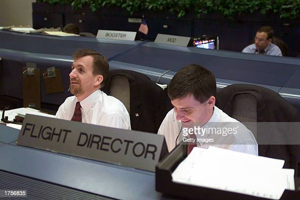 Flight Directors Leroy Cain and Steve Stich sit at their consoles in the shuttle flight control room in Houston's Mission Control Center is seen...