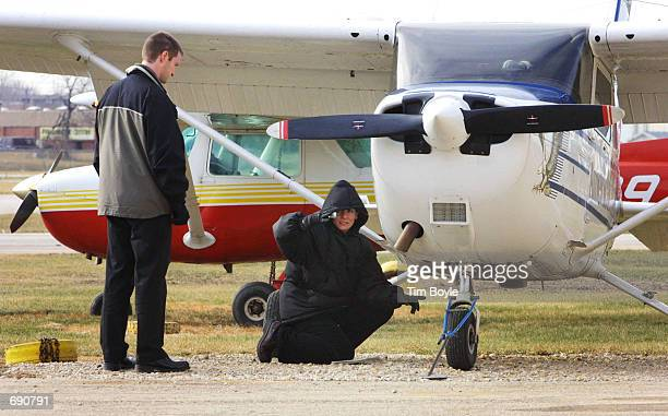A flight instructor watches a student perform a preflight check on a Cessna 172 before leaving the American Flyers Pilot Training School January 7...