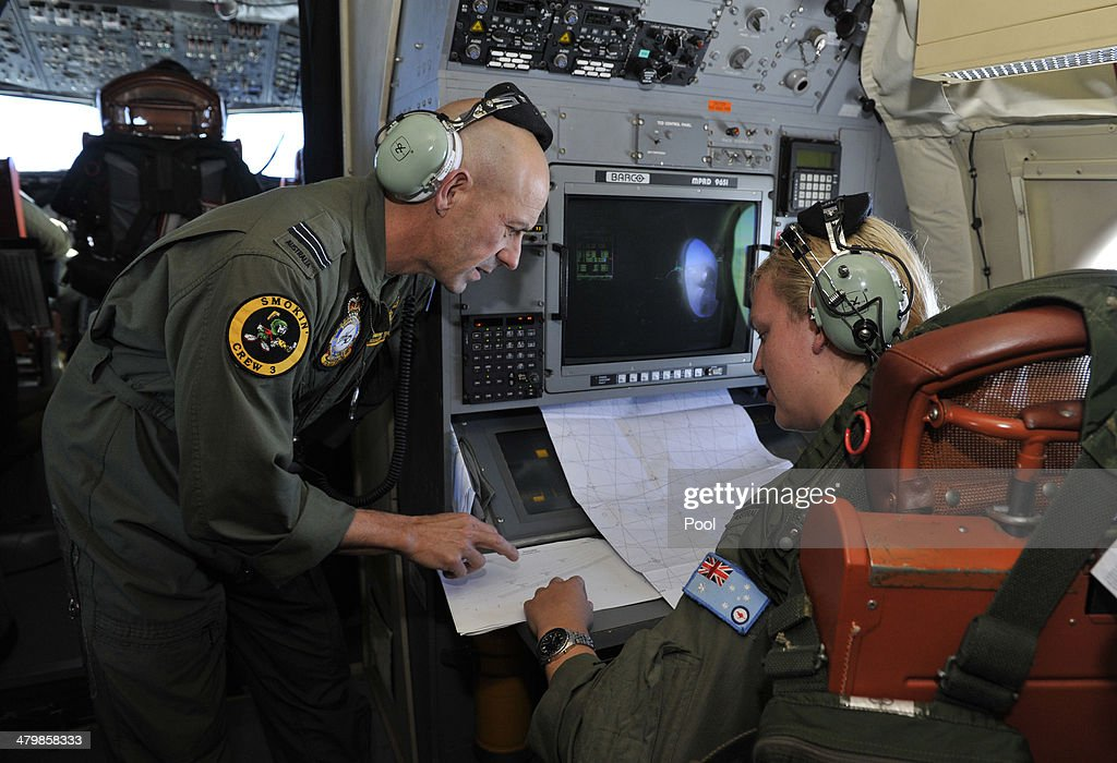 Flight Leuitenant Neville Dawson discusses the search area with Flight Officer Brittany Sharpe on board a Royal Australian Airforce AP3C Orion from...