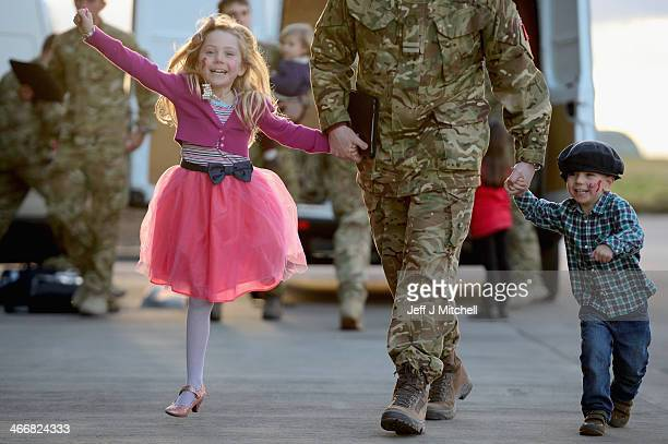 Flight Lieutenant Andy Power of 617 Squadron the Dambusters greets his daughter Jessica aged seven and son Harry aged three as he arrives back at RAF...