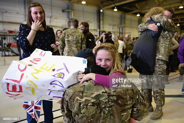 Flight Lieutenant Andy Power of 617 Squadron the Dambusters hugs his daughter Jessica aged seven as he arrives back at RAF Lossiemouth from...