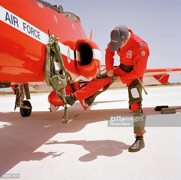 Flight Lieutenant Dan Simmons of the elite 'Red Arrows' Britain's prestigious Royal Air Force aerobatic team zips up his gpants before climbing into...