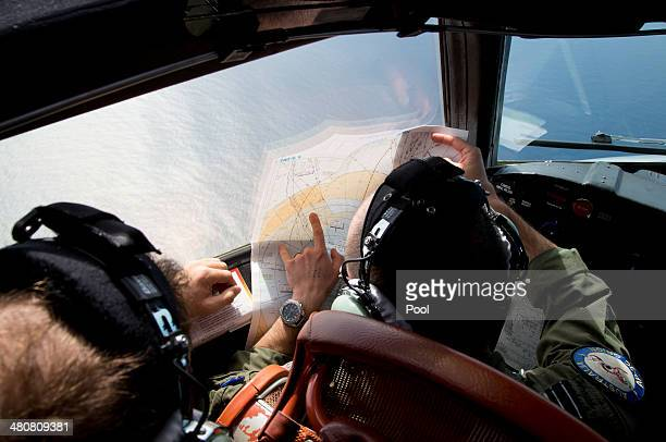Flight Lieutenant Jayson Nichols looks at a map as he flies aboard a Royal Australian Air Force AP3C Orion aircraft searching for missing Malaysian...
