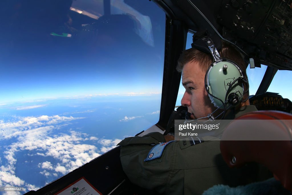 Flight Lieutenant Russell Adams looks out from the cockpit of an AP-3C Orion whilst on a search mission in the Southern Indian Ocean on March 26, 2014 in Perth, Australia. The search for flight MH370 resumes today after rough winds and high swells prevented crews from searching for debris yesterday. Six countries have joined the search, now considered to be a recovery effort, after authorities have announced that the airliner crashed in the Southern Indian Ocean and that there are no survivors.