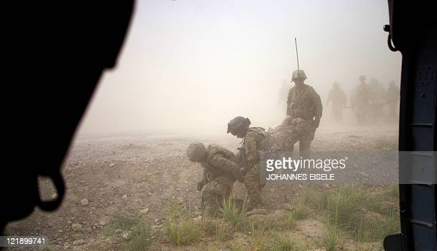 US flight medic Brandon Lowther helps US soldiers carry a wounded comrade to a Medevac helicopter from the 159th Brigade Task Force Thunder to be...