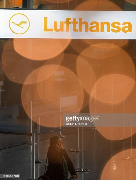 A flight passenger is seen behind an illuminated Christmas tree and a banner with the logo of German airline Lufthansa on November 24 2016 at the...