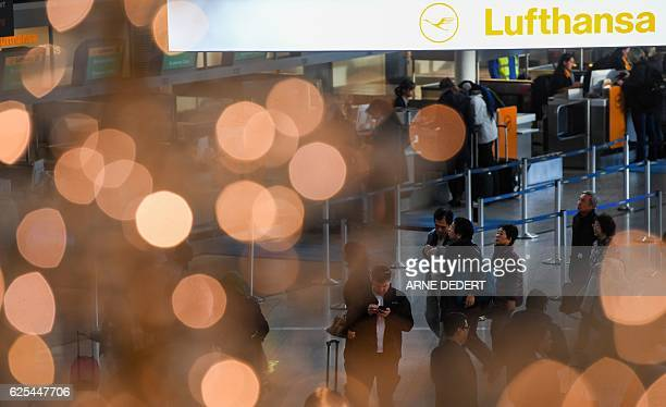 Flight passengers are seen behind an illuminated Christmas tree and a banner with the logo of German airline Lufthansa on November 24 2016 at the...