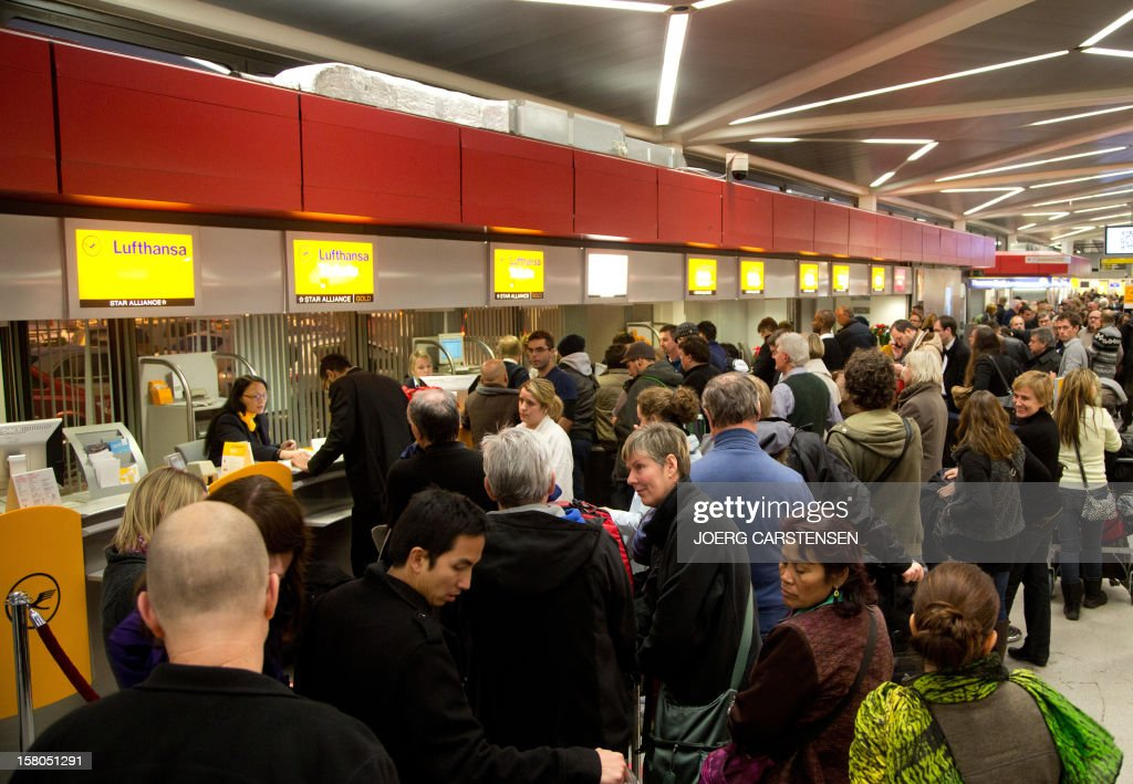 Flight passengers wait at Tegel airport in Berlin on December 10, 2012. Airport security personnel in Germany staged warning strikes in a dispute over pay, bringing disruption to several German airports. AFP PHOTO / JOERG CARSTENSEN GERMANY OUT