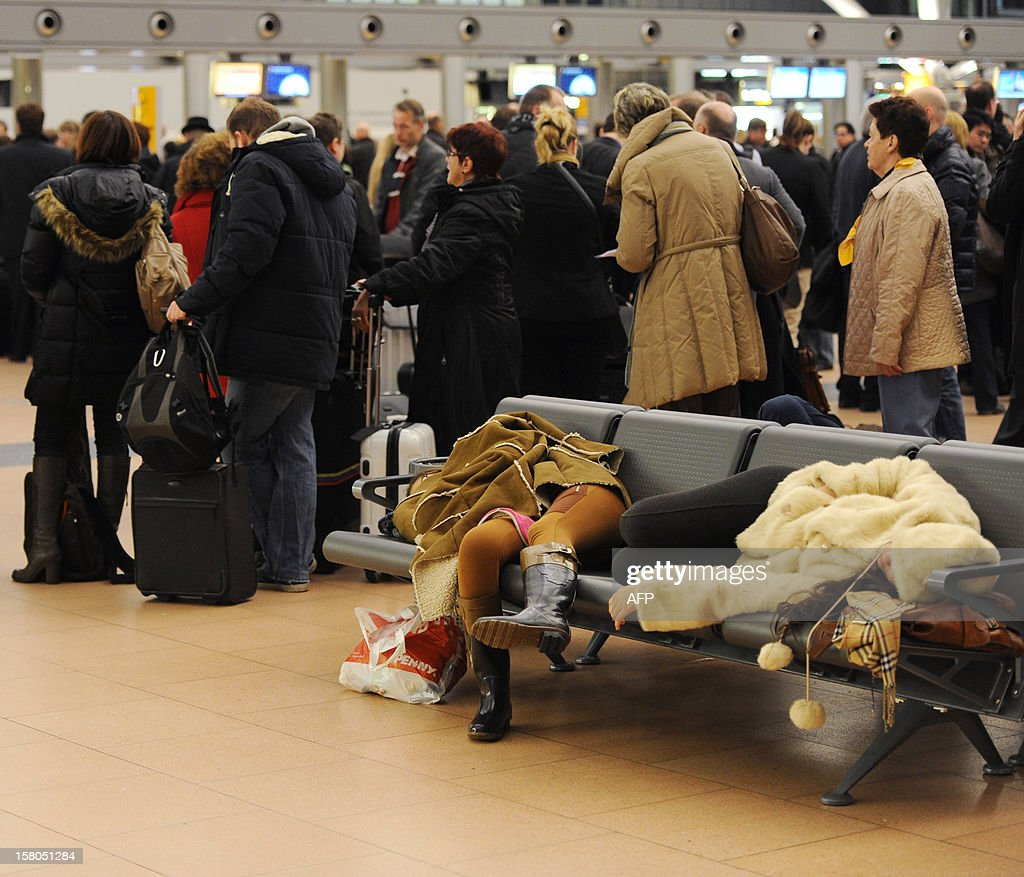 Flight passengers wait at the airport in Hamburg, northern Germany, on December 10, 2012. Airport security personnel in Germany staged warning strikes in a dispute over pay, bringing disruption to several German airports. AFP PHOTO / ANGELIKA WARMUTH GERMANY OUT