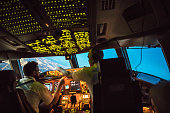 Two pilots at work during departure of Dallas Fort Worth Airport in United States of America. The view from the flight deck piont of view with high workload the beginning night through the wind shield