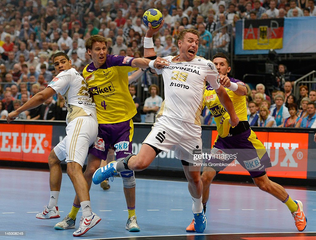 Fliip Jicha of Kiel throws the ball under the pressure of Torsten Laen and Alexander Petersson of Berlin during the EHF Final Four semi final match between Fuechse Berlin and THW Kiel at Lanxess Arena on May 26, 2012 in Cologne, Germany.
