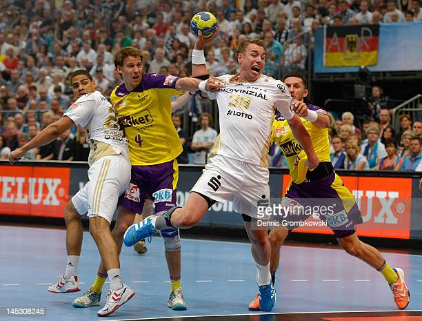 Fliip Jicha of Kiel throws the ball under the pressure of Torsten Laen and Alexander Petersson of Berlin during the EHF Final Four semi final match...