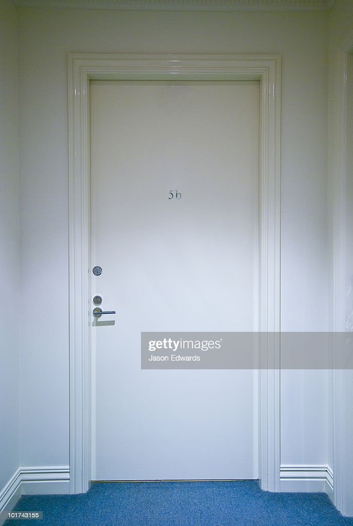 A closed white door at the end of a corridor leads to an apartment.