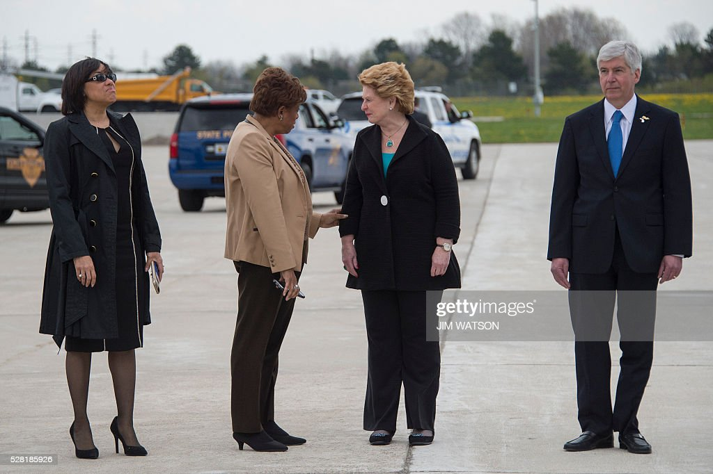 Flint Mayor Karen Weaver (L) and Michigan Governor Rick Synder (R) look on as US Senator Debbie Stabenow (2nd R), D-Michigan and US Congresswoman Brenda Lawrence (2nd L), D-Michigan, chat as they await the arrival of the US President at Bishop International Airport in Flint, Michigan, May 4, 2016. / AFP / Jim Watson