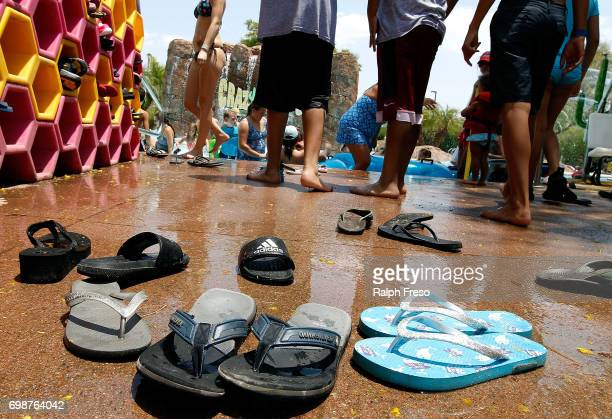 Flip flop sandals are left behind as visitors make their way into the water for relief from the heat at the WetNWild Water Park on June 20 2017 in...