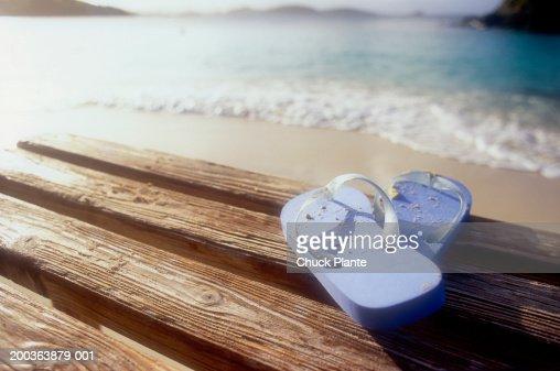 Flip flop sandals on dock at beach, close-up