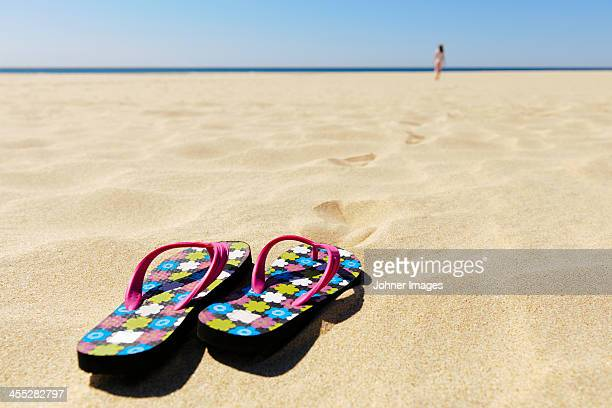 Flip flops on beach, girl on background