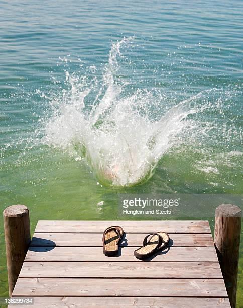 Flip flops on wooden deck by lake