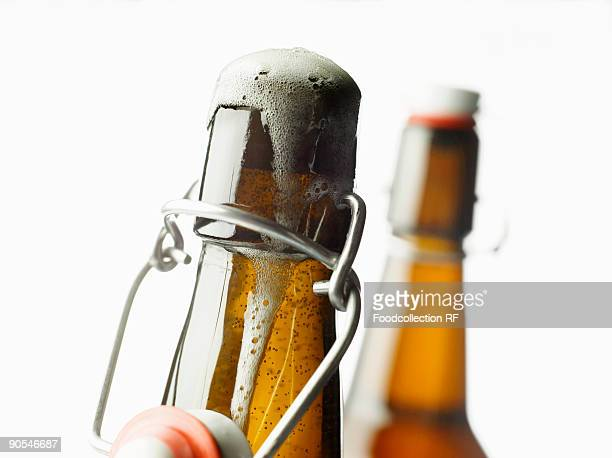 Flip top bottle with beer frothing out, close up