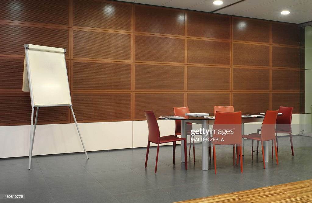 Flipchart and red chairs in conference room