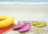 Flip-flops and inner tube on beach