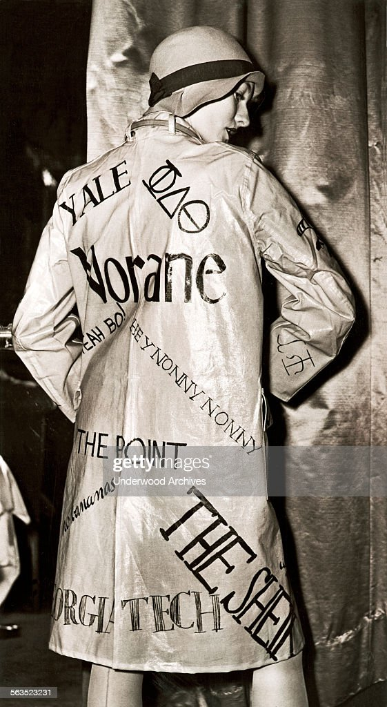 A flippant flapper at a rainwear fashion show wears a slicker of the era with painted phrases of the 'Roaring '20s' along with a deepcrowned cloche...