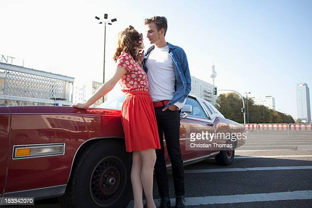 A flirtatious rockabilly couple standing next to a vintage car, Berlin, Germany