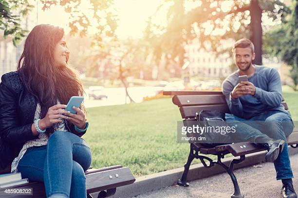 Flirting couple in the park texting on smartphones
