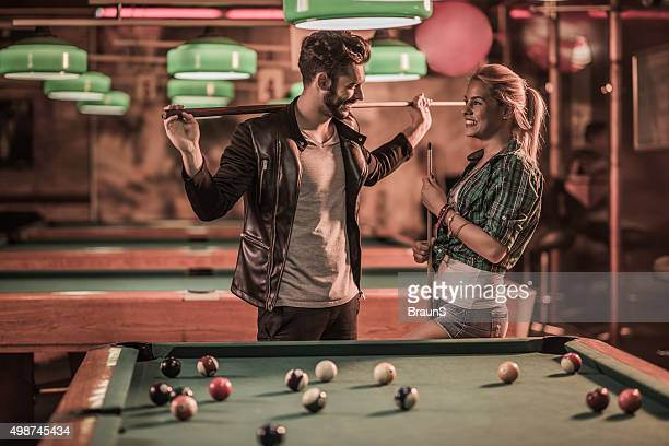 Flirty couple talking to each other in a pool hall.